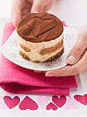 Hände servieren Tiramisu-Törtchen mit Herz im Kakaopulver