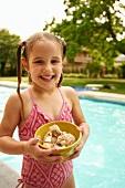 Kleines Mädchen mit einer Schale Eis neben einem Pool