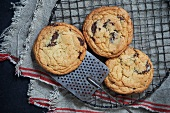 Three Chocolate Chip Cookies on a Cooling Rack with a Spatula