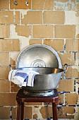Geschirrtücher in einer Metalwanne auf einem Hocker