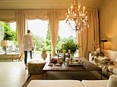 Elegante aber gemütliche Sitzecke mit ausladendem Überecksofa und Kronleuchter; Blick in Garten zwischen Vorhängen und als Schabracken drapierten Raffrollos