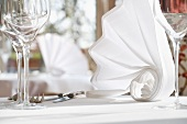 Artfully folded white napkins on a table laid for a meal