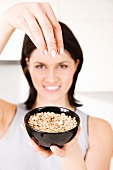 A woman holding up a bowl of porridge oats