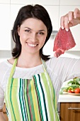 A woman holding up a raw steak in the kitchen