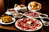 Starters from Italy: ham, salami, bread, olives, spread and sauces