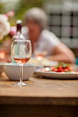 A glass of rosé wine on a table in the garden