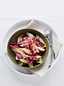 A salad of chicory with fruit and dry-cured ham