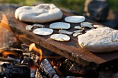 Chapati being baked on hot metal over an open fire