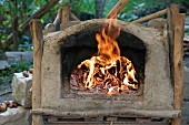 A clay oven with a fire burning inside