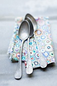 Three spoons on a patterned cloth