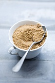 Brown sugar in a cup with a spoon
