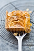 A piece of orange tart with slivered almonds on a spatula