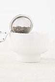 A tea strainer balanced on a white tea bowl