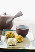 Chocolate truffles with pistachios and white chocolate, with a bowl of tea and a teapot