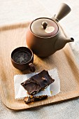 Almond brittle with dried fruit and chocolate, with a cup of tea and a teapot