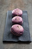 Three purple macaroons on a paper napkin