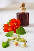Nasturtium leaves and flowers in front of a bottle of vinegar