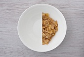 A halved portion of cornflakes in a white bowl (view from above)