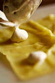 Ravioli being filled with cream cheese (close-up)