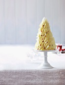 A white chocolate cake in the shape of a Christmas tree