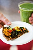 Wholemeal pizza with raw vegetables and a green smoothie