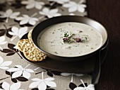 Cream of mushroom soup with herb flowers and crackers