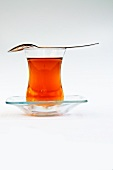 Asian tea in a tea glass with a spoon lying on the top