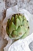 An artichoke in baking parchment