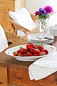 Fresh strawberries in a white porcelain dish on a vintage wooden table