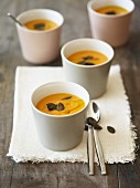 Several portions of pumpkin soup topped with pumpkin seeds