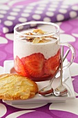 Vanilla custard with strawberries and sliced almonds; served with almond biscuits