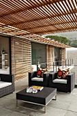 Modernes Wohnhaus mit eleganten schwarzen Outdoormöbeln auf Terrasse unter Pergola aus Holzleisten und Holzjalousien vor der Glasfront