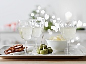 White wine spritzer in wine glasses with nibbles