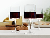 Glasses of red wine in front of a cheeseboard