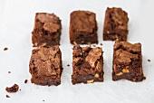 Six chocolate brownies on paper