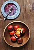 A Wooden Bowl of Blood Oranges with Peel; Dirty Plate with a Fork; From Above