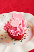 Pink Frosted Cupcake with Pink Hearts and Confetti Sprinkles; On a White Plate