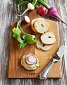 Hummus and Sliced Radishes on a Bagel Crisp; Bagel Crisps on a Cutting Board