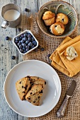 Fresh Blueberries with Blueberry Scones and Blueberry Muffins on a Wooden Table; From Above