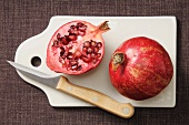 A whole and a half pomegranate on a chopping board with a knife