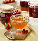 Assorted jams in jars and in a glass bowl