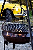 A barbecue, with a yellow classic car in the background