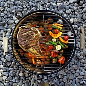 A T-bone steak and vegetables on the barbecue