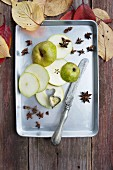 Slices of pear with star anise and a small shaped cutter on a tray