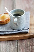 Coffee in a tin cup with a pear tartlet