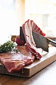 Raw pork ribs with a cleaver on a wooden board