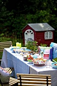 A table laid with cinnamon whirls and strawberries in the garden for a party on Midsummer day