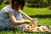 Mädchen bestäubt mit Puderzucker frisch gebackene Kanelbullar (Schwedische Zimtschnecken) auf dem Rasen