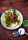 Köfte (Turkish meatballs) on a bed of lettuce leaves with mint yoghurt