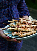 A woman holding a plate of barbecued chicken satay skewers